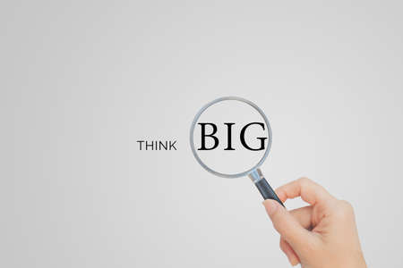 Big Thinking Concept : Hand holding magnifying glass and looking to THINK BIG wording text om gray background.
