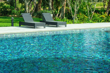 Tropical view of blue water in swimming pool with black weave daybed and green trees in background. 版權商用圖片