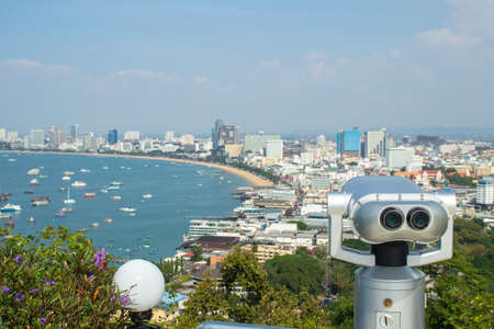 Binocular or telescope locate on viewpoint for support traveler use looking for view of Pattaya city from Pratumnak Hill Viewpoint, Chonburi, Thailand.