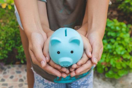 Money Savings Concept : Hands hold blue piggy bank. Reklamní fotografie - 161227022