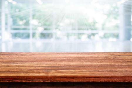 Side view of Empty space wooden table top with blurred inside room background.