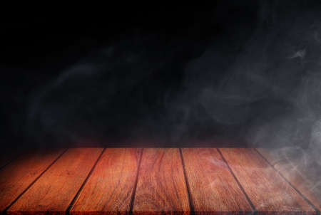 Side view of Empty space of Wooden table top with smoke or mist in black background. 版權商用圖片