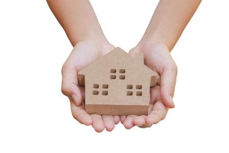 Real Estate Concept : Hand holding wooden home model toy isolated on white background. (Clipping path)