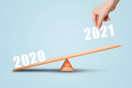 Business Planning and New Years 2021 Concept : Hand hold text wording 2021 and putting on the side of wooden balance scales or seesaw.