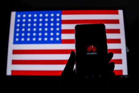 PERAK, MALAYSIA - MAY 24, 2019: A man holds an android-smartphone that shows the Huawei logo in front of the USA flag. Google is restricting Huaweis access to its Android system. Editorial