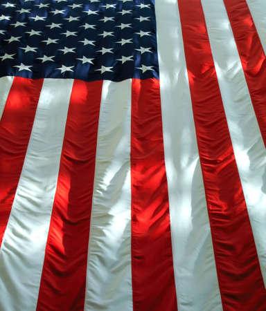 Colgado verticalmente bandera americana con luz y sombras.  Foto de archivo - 3293873