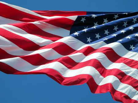 Waving American flag against a blue sky background. Stock Photo - 3294143