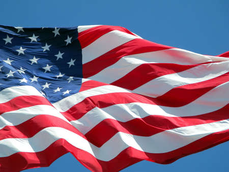 Waving American flag against a blue sky background. Stock Photo
