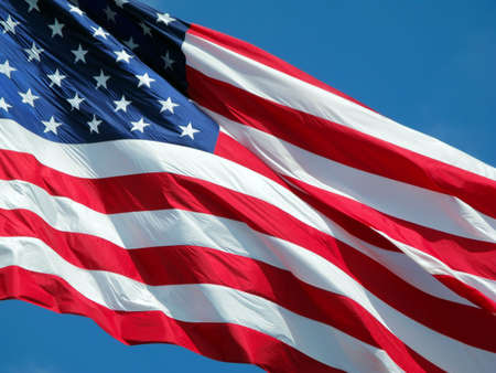 Waving American Flag against a blue sky background. Stock Photo - 3294140