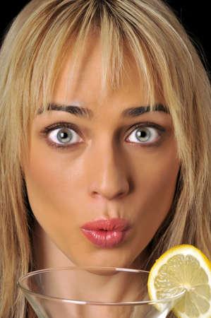 Beautiful blonde woman looking over martini glass with lemon. Imagens
