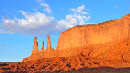 mesa: Three Sisters rock formation and Mitchell Mesa in Monument Valley on the border of Arizona and Utah. Stock Photo