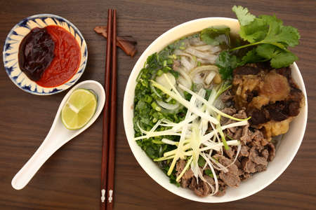 Vietnamese rice noodles are served with beef, onion, lime, hoisin sauce and chili sauce  photo