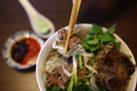 Vietnamese rice noodles are served with beef, onion, lime, hoisin sauce and chili sauce