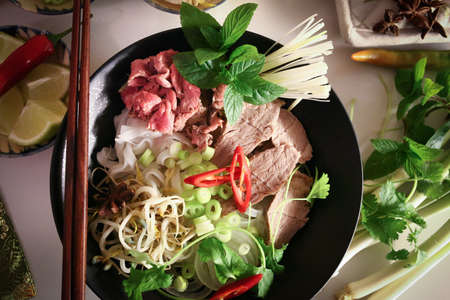 Preparing Pho, Vietnamese rice noodles, with beef and other materials