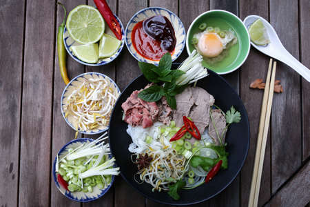 hoisin sauce: Vietnamese rice noodles are served with beef, lime, hoisin sauce and chili sauce and ready to eat.