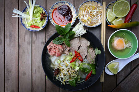 hoisin: Vietnamese rice noodles are served with beef, lime, hoisin sauce and chili sauce and ready to eat  Stock Photo