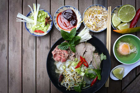 Vietnamese rice noodles are served with beef, lime, hoisin sauce and chili sauce and ready to eat  Stock Photo