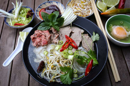 Vietnamese rice noodles are served with beef, lime, hoisin sauce and chili sauce and ready to eat  photo
