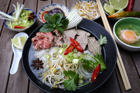 Vietnamese rice noodles are served with beef, lime, hoisin sauce and chili sauce and ready to eat  Standard-Bild