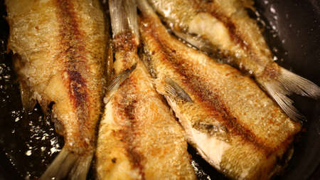 Fishes are fried on a pan at high temperature photo