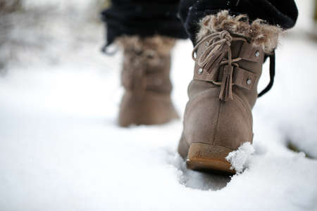 Girl walking on the snow with boots in the afternoon Standard-Bild