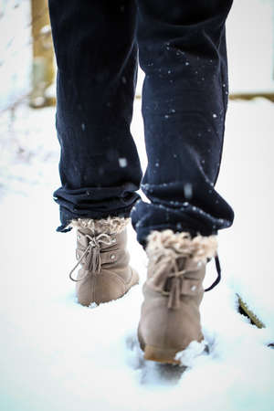 Girl walking on the snow with boots in the afternoon photo