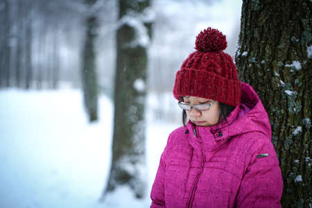 Young and moody asian girl with a pink jacket leaning against a tree in the winter photo