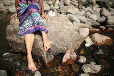 Young asian girl in a colorful maxi dress playing by a river in the summer photo