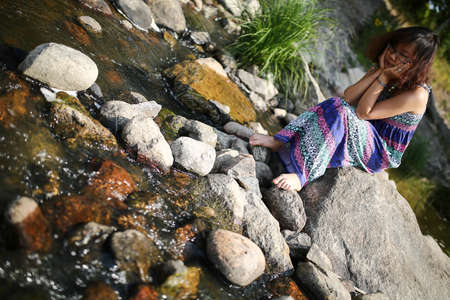 maxi dress: Emotinal asian girl in a maxi dress sitting on a rock by a river in the summer Stock Photo