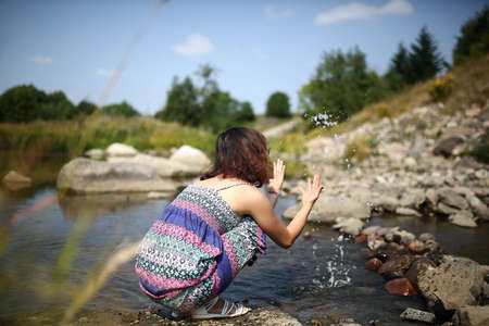 maxi: Young asian girl in a colorful maxi dress playing by a river in the summer