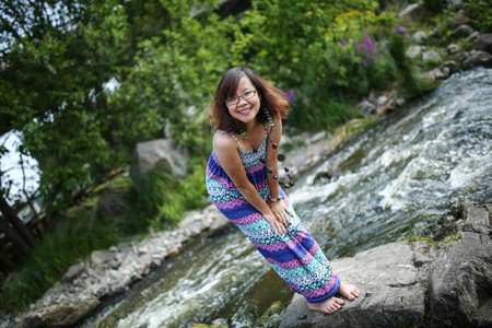 maxi dress: Young asian girl in a colorful maxi dress playing by a river in the summer