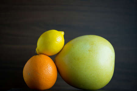 pummelo: Citrus fruits include pomelo, lime, and orange are mix in a closeup view.