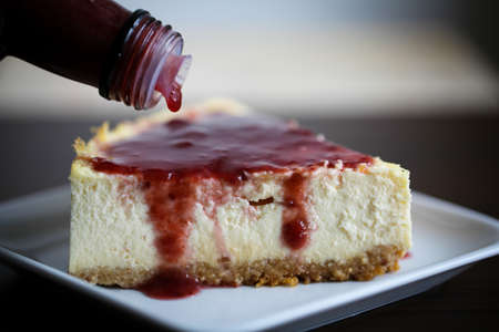 New York style cheesecake slice with raspberry syrup