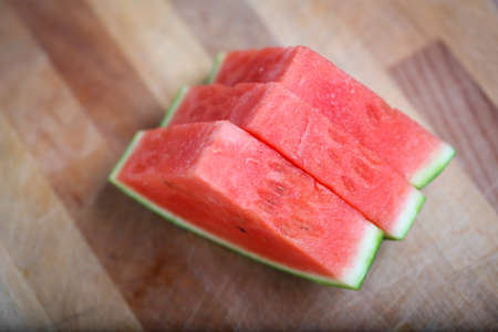 Fresh slices of red watermelon on a wooden surface in a closeup view. Selective focus.