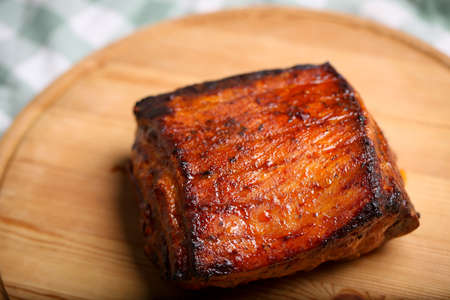 Piece of roasted pork on a wooden board in a closeup view