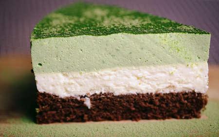 porcion de torta: Un pedazo de matcha  té verde, polvo de coco y pastel de chocolate en una vista de primer plano. Foto de archivo