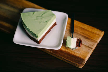 A piece of matcha/green tea, coconut powder, and chocolate cake in a closeup view.