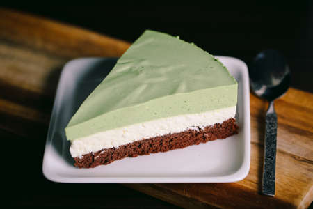 green powder: A piece of matchagreen tea, coconut powder, and chocolate cake in a closeup view.