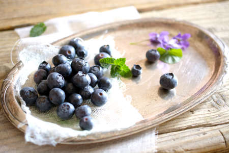 silver tray: Blueberries, violets and mint leaves on silver tray