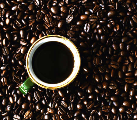 high angle: Cup of coffee standing on coffee beans, high angle Stock Photo