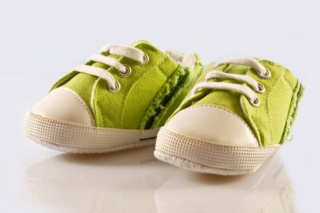 Green baby shoes on a white background photo