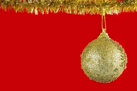 Christmas golden ball on a red background 写真素材