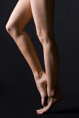 nude woman standing: Bare legs on a black background
