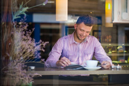 fashion magazine:  Portrait of a young man reading and drinking coffee Stock Photo