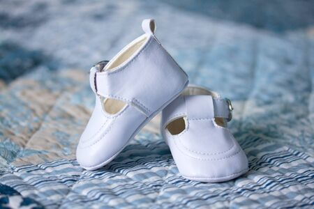 White baby shoes on a blanket