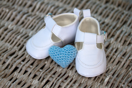 crotchet: White baby shoes and a blue crotchet heart