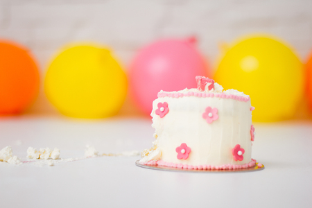 Smashed first birthday cake and balloons Stock Photo