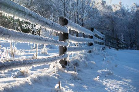 Frozen wooden fence, winter landscape in Poland