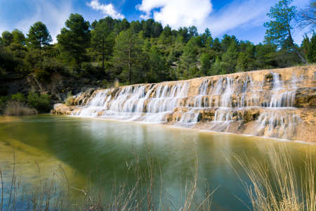 River waterfall with a pine forest and clouds background