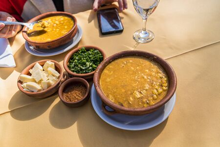 Locro, typical Argentine food, accompanied by bread and a glass of wine, with spoons.